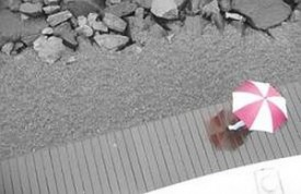 Pink and white umbrella by beach